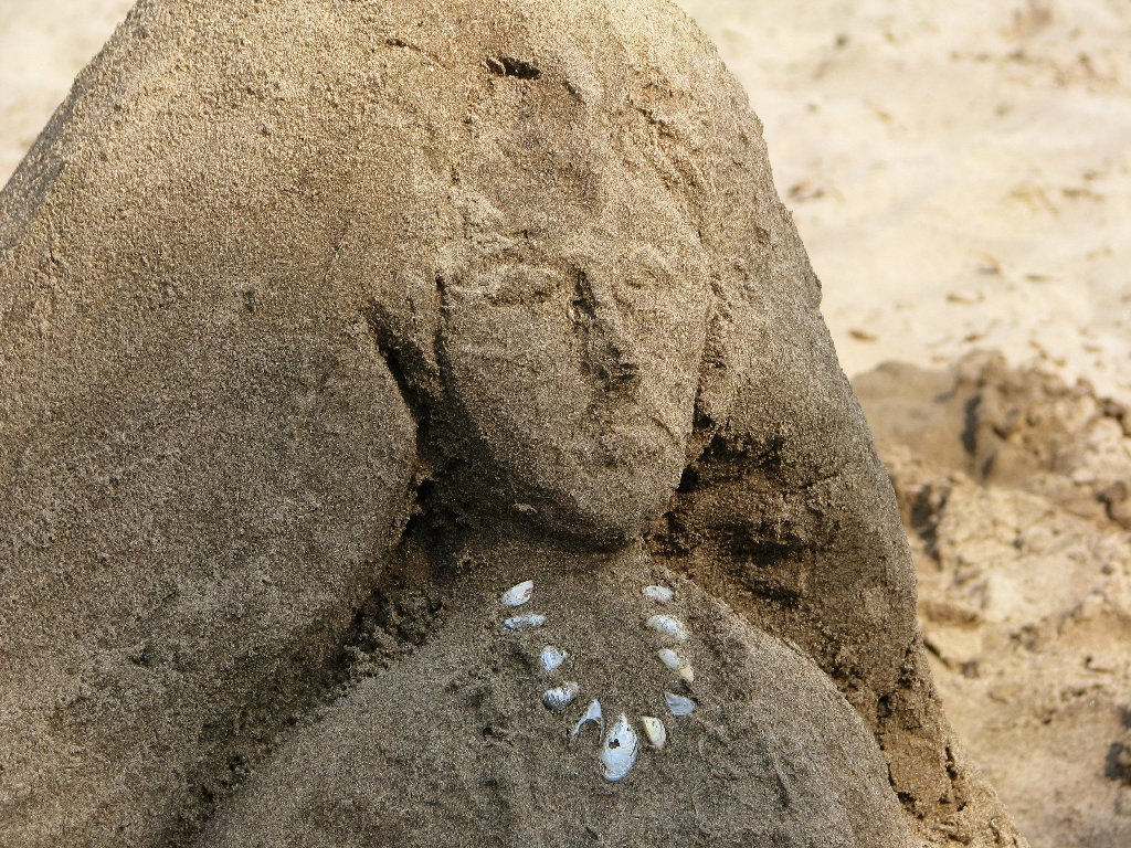 Close on the mermaid's face, and her inset pebble necklace